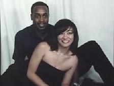 Niqui is posing with her fiance, a African American man wearing a black shirt and dark pants.