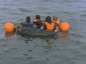 Four men packed into a small life raft, there are two large orange bouys attached to the raft.