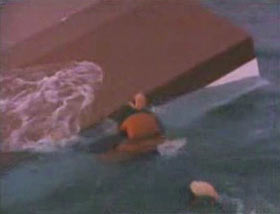 A man in an orange life vest holding onto the overturned hull of a ship.