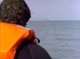 A man in an orange life vest looks out over the water.