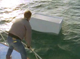 A man is standing on a boat, leaning over the railing trying to reach a large white box that is floating.