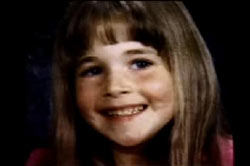 A young girl, Morgan Nick, posing for a school picture. She has long brown hair with bangs.