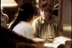 A woman with short brown hair is seated and talking to a woman with long dark hair.