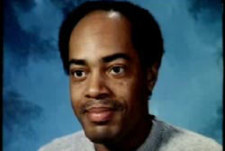 An African American, Oliver Munson. He has a receding hairline and is posing in front of a blue bakcdrop.