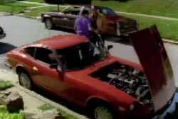 Two men stand next to a red compact car, the hood is open and the engine is visible.