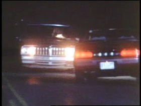 A dark road with two cars parked facing each other.