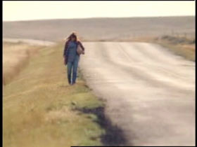 A woman with a bag over her shoulder walking down a remote road.