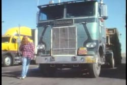A woman in a purple plaid shirt walking past the front of a semitruck.