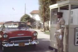 A red convertible pulls up to a security guard standing outside a security booth.