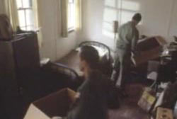 Two men packing up a small bedroom.