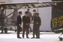 Four men in suits and hats standing near military aircrafts.