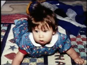A baby, Sabrina Aisenberg, in a blue jumpsuit playing on a blanket.