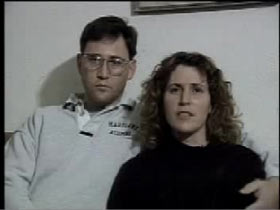 Sabrina's parents sitting on a couch. Steve has short brown hair and Marlene has shoulder length wavy brown hair.