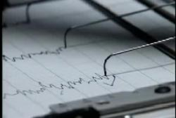 A close up image of a polygraph test. The needles are drawing the lines on the paper.