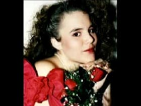 Star Palumbo wearing a off the shoulder red dress and holding three roses close to her face.