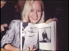 Susan Walsh posing holding open a book to show a piece of artwork she did.