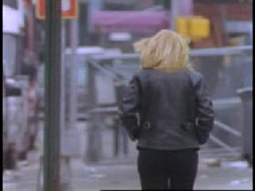 A woman with blonde hair and a leather jacket walking away down a street.