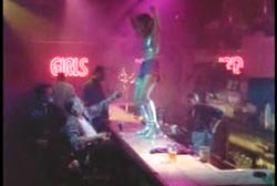 A dancer dancing on a bar in a strip club as several people look up at her.