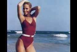 Tami Lynn Leppert posing on the beach in a red one piece bathing suit.