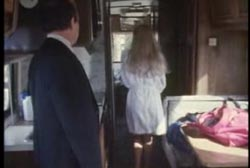 A woman in a robe walks down the hall of a mobile home as a man in suit watches her.