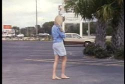 A woman without shoes walking through an empty parking lot.