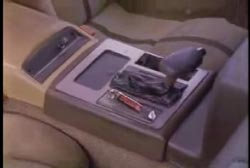 A close up on the center console on a car, showing the gear shift and a can of mace next to it.