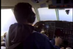 A pilot in the cockpit of a small plane.