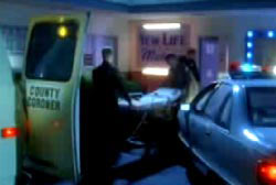 Two coroners roll a gurney from their car into a building.