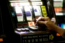 A person slipping a coin into a slot machine