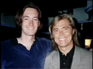 Joe with his arm around his father, Dennis Cole. Both had long hair and are smiling