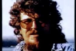 Tom Roche with long curly hair beard and glasses