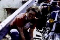 Tom Roche crouching down next to a motorcycle