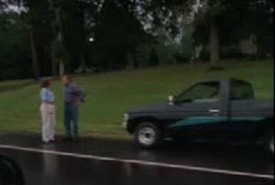 Two people standing in front of a pick up truck that is parked on the shoulder of a street.