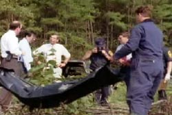 Several detectives stand by as two coroners lifting a black body bag out of the grass.