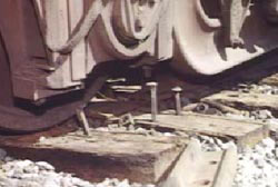 A close up on the tracks where several large nails are sticking up out of the tracks.