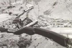 A black and white photo of the derailed train from a different angle.