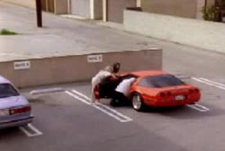 Two people leaning into a red compact car parking in an empty parking lot.