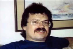 A middle aged caucasian man, David Merrifield, with short brown hair, a mustache, and large wire rimmed glasses.