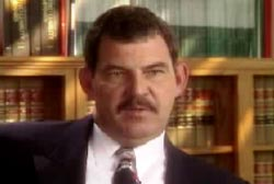 A middle aged caucasian man, Sgt. King, wearing a suit and sitting infront of a bookcase filled with legal books.