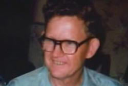 A middle aged caucasian man, Dexter Stefonek, with short curly hair and large glasses.