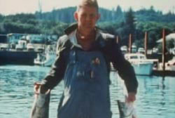 Dexter stands on a dock holding up two large fish.