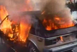 A small compact car engulfed in flames.