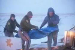 Three police officers carry a body bag to an ambulance.