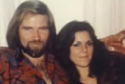 A young caucasian couple on a couch. Diana Robertson and Mike Riemer, Diana has long brown hair and Mike has long blonde hair.