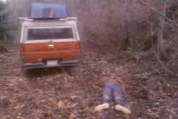 A body is laying face down on the ground in a forest, there is a truck parked nearby.
