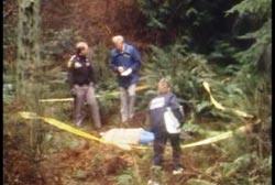 Three police officers stands next to the corpse, covered by a white sheet. There is crime scene tape circling the area.