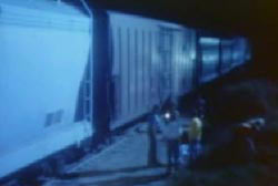 Investigators searching for a green tarp next to the train