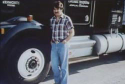 Smiling Dwayne McCorkendale with a mustache standing next to his semi-truck