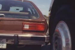 A brown pinto car bumping into the front of a semi truck