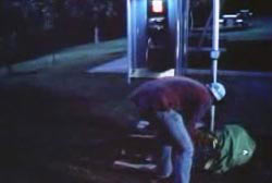 A man picking up stuff from the ground by a payphone
